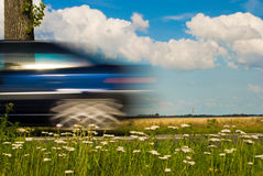 Blue Car Driving By Stock Photos