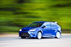 Blue car driving fast on country road stock image