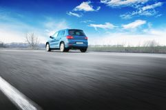 A blue car driving fast on the countryside road against sky with stock photography