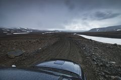 Blue car driving in highlands Iceland view over the car hood stock image