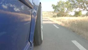 Blue car driving on a mountain road with white wheels stock video footage