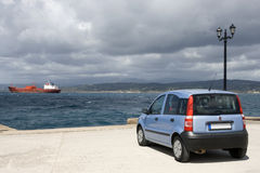 Blue car in front of the heavy sea. Peloponnese - Harbor of Pylos Royalty Free Stock Photography