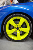 Blue car with green alloy wheel indoor Stock Images