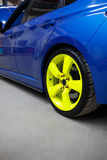 Blue car with green alloy wheel indoor Stock Photos