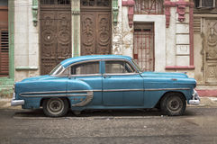 Blue car in Havana on a rainy day. An old american car parked in Central Havana on a rainy day royalty free stock photo
