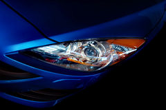 Blue car headlight. A closeup of the stylish headlight of a dark blue, modern car Royalty Free Stock Image
