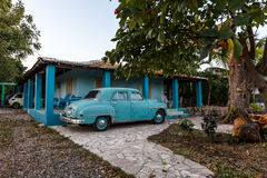Blue Car and Home. Blue vintage car parked in front of tropical home in Trinidad, Cuba Stock Photos