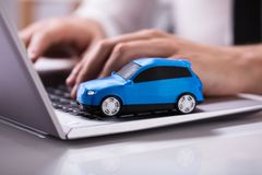Blue Car On Laptop Keypad. Close-up Of A Small Blue Car On Laptop Keypad stock photos