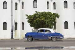 Blue car in Old Havana, Cuba. American classic car running in front of the Ortodox Church in Old Havana, Cuba stock image