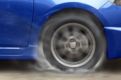 Blue car racing spinning wheel burns rubber on floor. Stock Photo