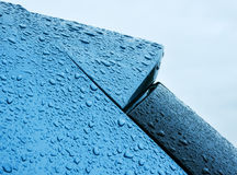 Blue car in the rain shower. Raindrops retained on blue metallic paintwork of a car stock image