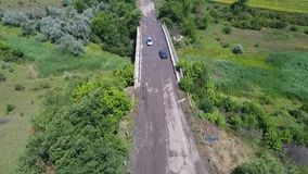 Aerial shooting, the drone takes off over a dirty road through a field. Blue car rides on muddy road through field stock video footage