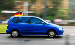 Blue car with soccer fan flag on roof Stock Photo