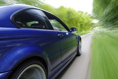 Blue Car Speeding. Blue Car Speeds Through a Coubtry Lane Royalty Free Stock Photos