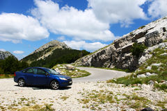 Blue car standing near mountain road. Blue sedan car is standing with doors open near a beautiful road through mountains. White rocks and lots of vegetation can Royalty Free Stock Photography