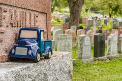 Blue car toy on a tombstone in a cemetary, symbolizing the death Stock Images