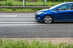 Blue car on uk motorway in fast motion.  stock image