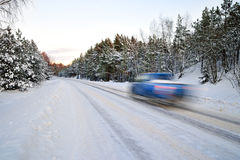 Blue car on winter road Stock Photos