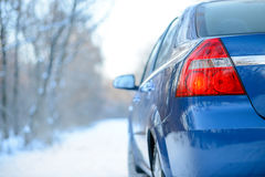 Blue Car on the Winter Snowy Road. Close up Rear View. Travel and Drive Safe Concept. Stock Images