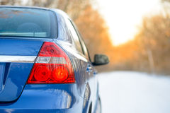 Blue Car on the Winter Snowy Road at Sunset. Close up Rear View. Travel and Drive Safe Concept. Stock Images