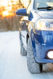 Blue Car with Winter Tires on the Snowy Road. Drive Safe. Royalty Free Stock Photos