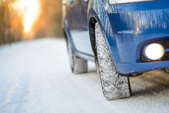 Blue Car with Winter Tires on the Snowy Road. Drive Safe. Stock Photo