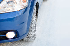 Blue Car with Winter Tires on the Snowy Road. Drive Safe. Space for Text. Stock Photography