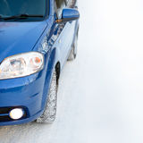 Blue Car with Winter Tires on the Snowy Road. Drive Safe. Space for Text. Stock Image