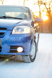 Blue Car with Winter Tires on Snowy Road at Sunset with Bright Sun. Travel and Safe Driving Concept. Royalty Free Stock Photo