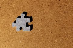 Blue cardboard puzzle piece on brown background. Blue cardboard puzzle piece on brown wooden background stock photography