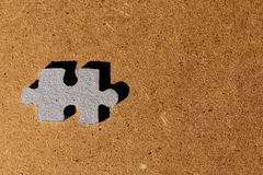 Blue cardboard puzzle piece on brown wooden background royalty free stock image