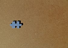 Blue cardboard puzzle piece on brown wooden background stock photos