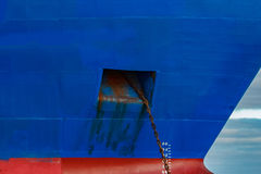 Blue cargo ship moored. In still Baltic sea water stock images