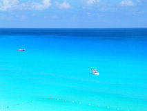 Blue Caribbean. The Caribbean Sea off Cancun in Quintana Roo, Mexico with two boats moored offshore and swimmers in foreshore. The brilliant pale color is due to royalty free stock photo