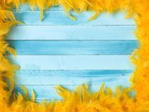 Blue carnival background with yellow feathers stock images
