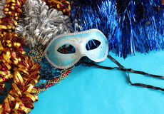 Blue carnival mask on a blue background with festive decorations. Stock Photos