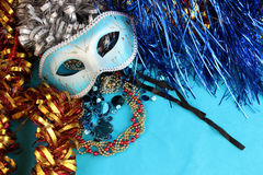Blue carnival mask on a blue background with festive decorations. Royalty Free Stock Photography