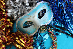 Blue carnival mask on a blue background with festive decorations. Stock Image