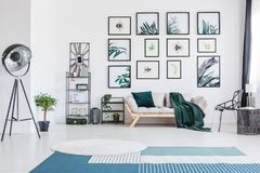 Living room with metal lamp. Blue carpet in bright living room with metal lamp and green blanket on sofa against wall with posters stock photography