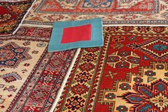 Blue carpet with red frame. And other valuable oriental carpets on sale in the boutique Stock Photography
