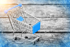 Blue cart from the grocery store on the old wooden background. New Year and Christmas buying. Empty shopping trolley. Business ideas and retail trade stock image