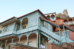 Blue carved wooden balcony under city fortress hill. Tbilisi, Old Town Stock Image