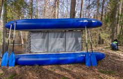 Blue catamaran with four oars  near trees in the forest. Inflatable blue catamaran with oars is leaning against the trees in the forest Stock Photography