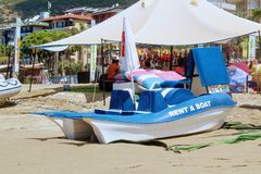 The blue catamaran pedal boat is stylized under the bodies of dolphins with the inscription `Rent a boat` on a sandy beach.  Royalty Free Stock Photography