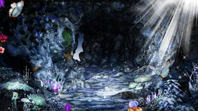 Blue cave with sun rays. Magic cave with crystals, mushrooms and butterflies Royalty Free Stock Photo