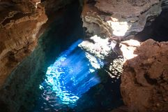 Blue cave with sunray lights. Scenic cave filled with a blueish transparent water, with a direct sunray light, in the Diamond Plateau Chapada Diamantina region stock photography