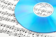 Blue CD or DVD on sheet music royalty free stock photography