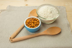 A blue ceramic bowl with almonds, a glass bowl with flour, woode Stock Image