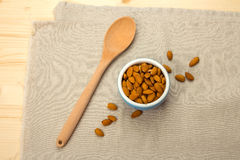 A blue ceramic bowl with almonds and a wooden spoon Royalty Free Stock Photography