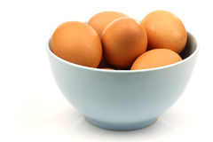 A blue ceramic bowl with brown eggs Royalty Free Stock Image